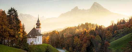 Eine Kapelle befindet sich vor einer bewaldeten Bergkulisse in der Dämmerung