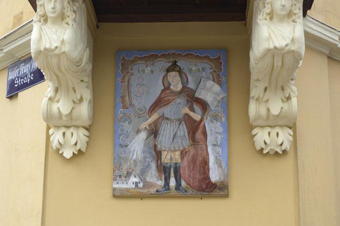 Heiliger Florian - Ein Gemälde des heiligen Florian hängt an einer Hauswand
