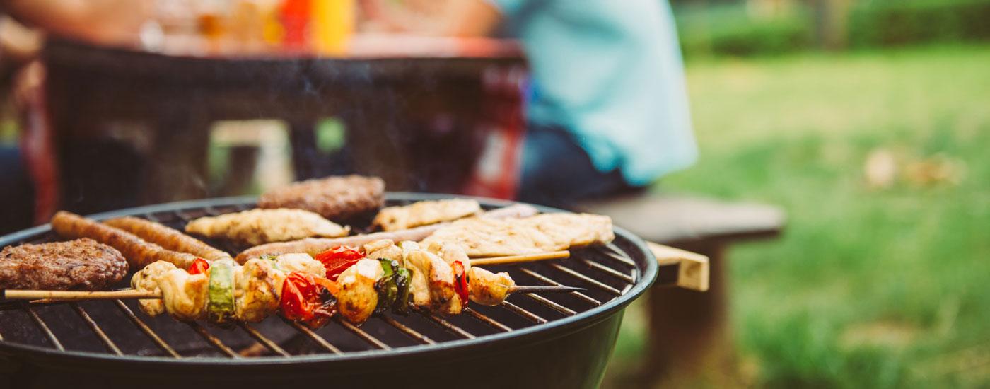 Ein Grill mit Fleisch und Spießen im Vordergrund, eine Gruppe von Menschen im Hintergrund