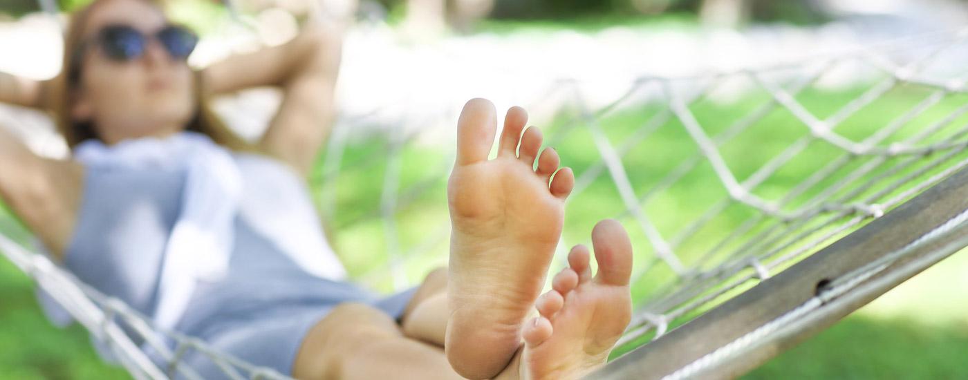 Sommerbeschwerden: Frau liegt in Hängematte und ist entspannt