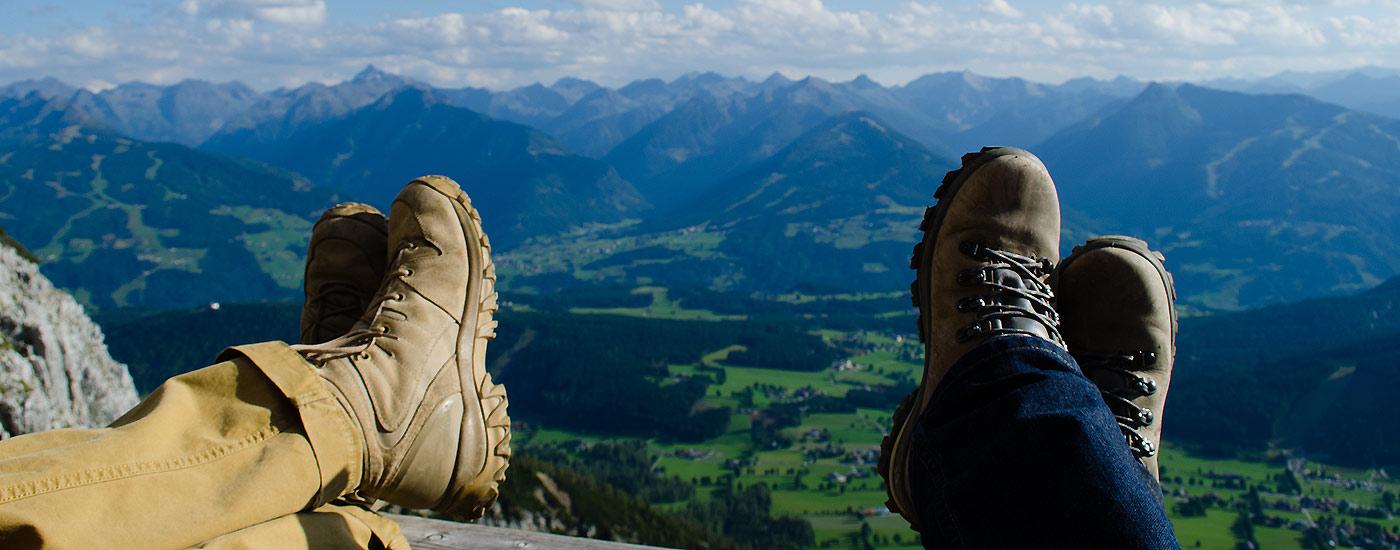 Blasenfrei Wandern: Wanderer haben Füße hochgelegt vor Bergpanorama