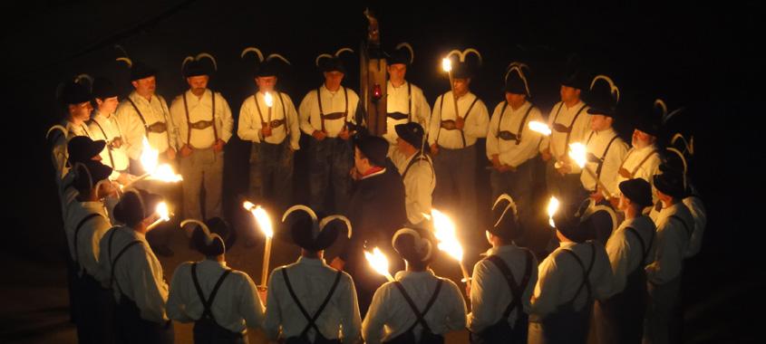 Kirchweih: Männer mit Falken stehen bei Dunkelheit im Kreis