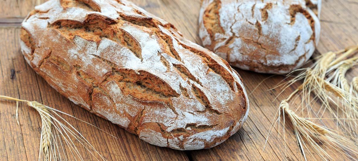 Brot einfrieren: Zwei Brotlaibe und Getreideähren auf einem Holzbrett